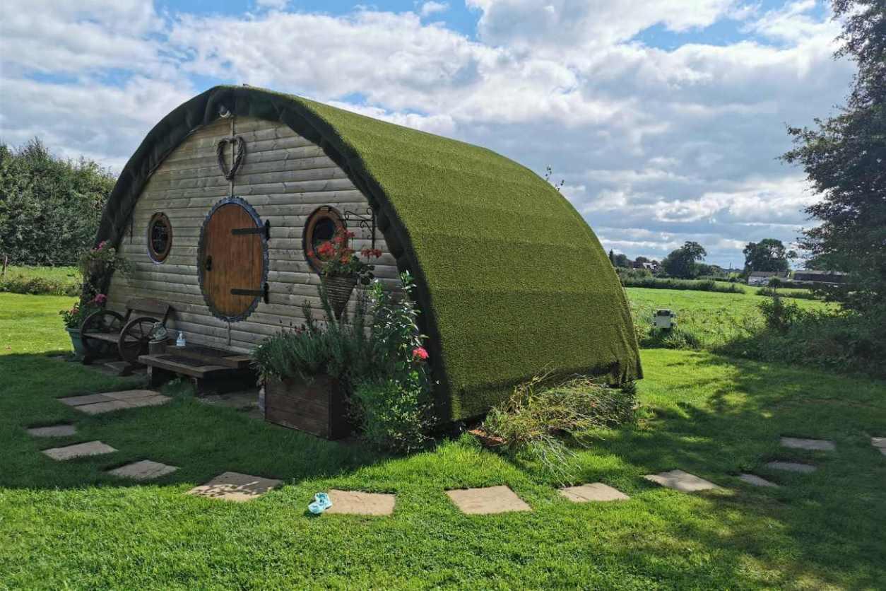 exterior-of-hobbit-retreat-cabin-in-field