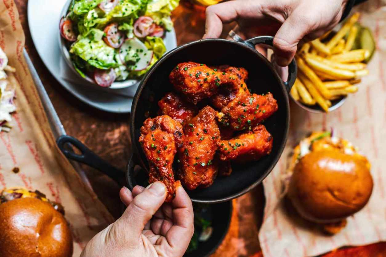 hands-holding-bowl-of-chicken-wings-at-the-blues-kitchen