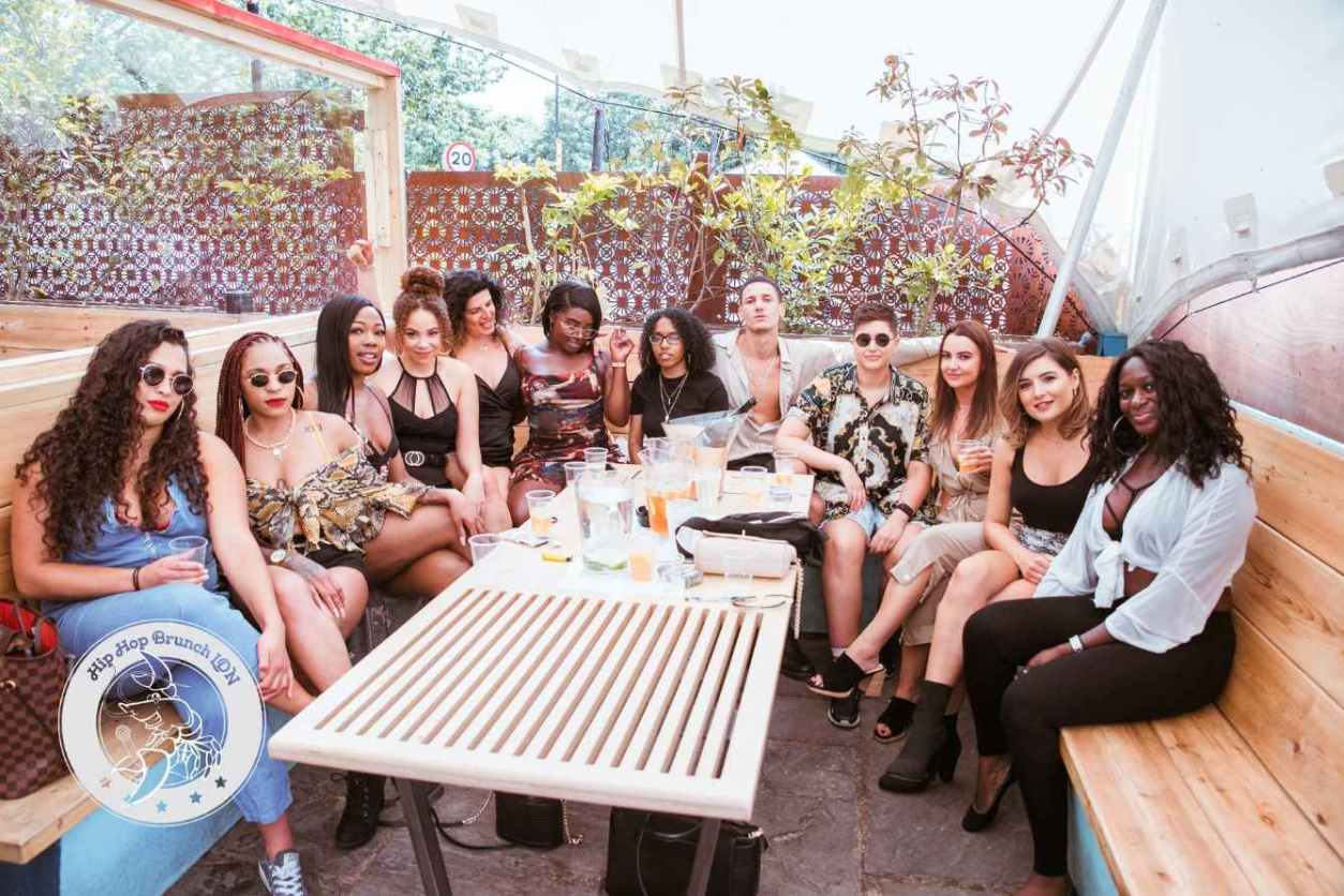 large-group-of-friends-drinking-around-table-at-hip-hop-brunch-bottomless-brunch-brixton