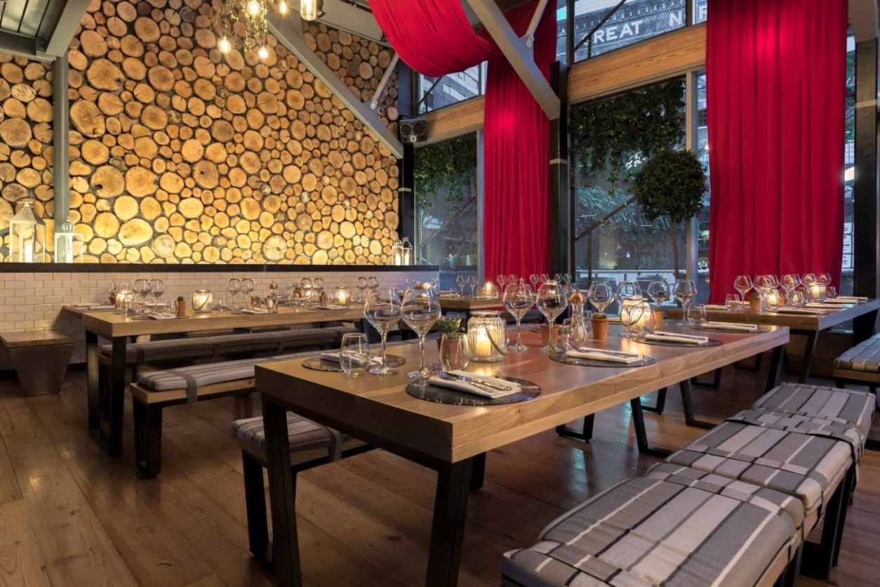 tables-with-wine-glasses-and-benches-in-impossible-bar