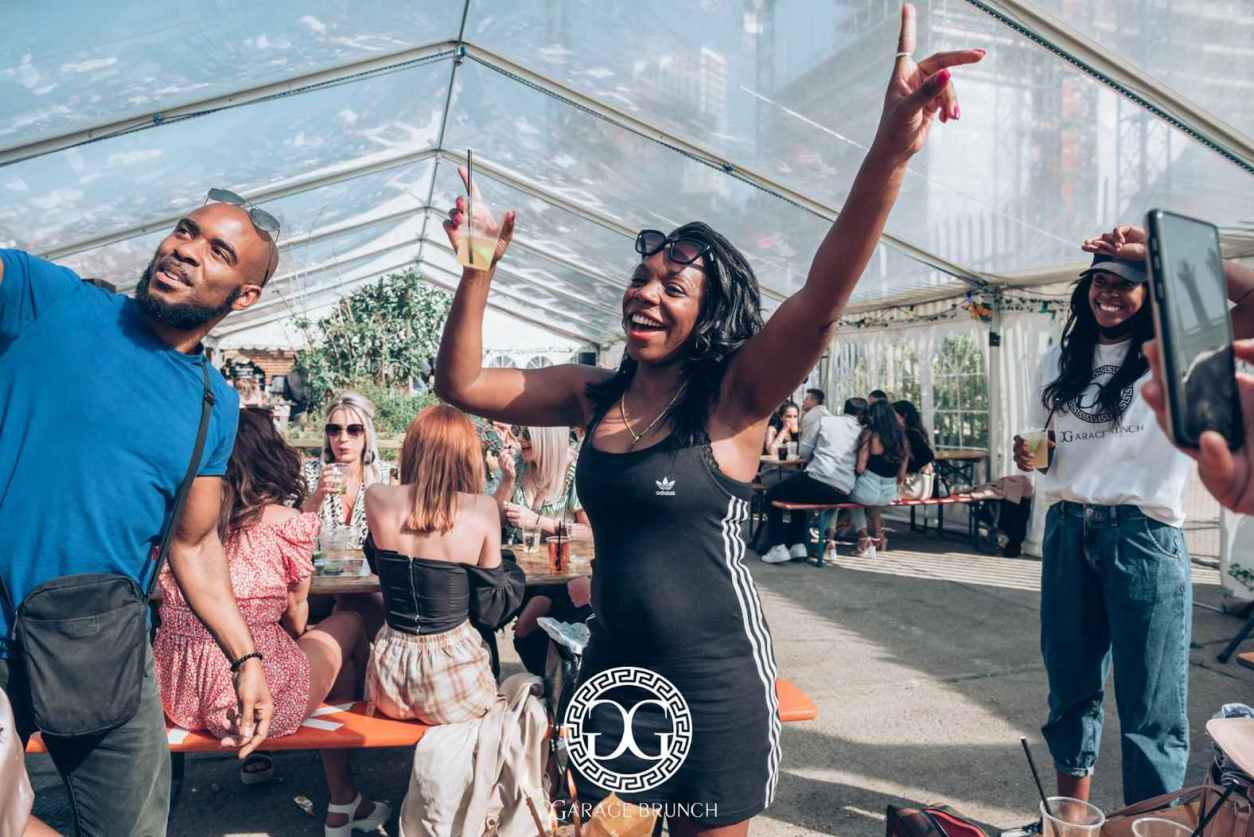 woman-dancing-with-drink-in-hand-at-garage-brunch