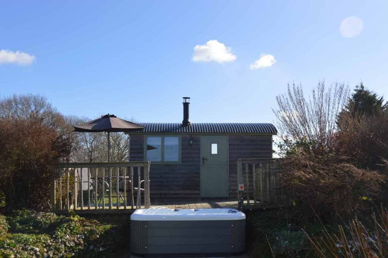 exterior-of-rose-shepherds-hut-with-outdoor-hot-tub