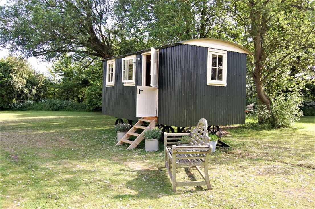 huntingfield-hut-shepherds-hut-in-field-with-bench-glamping-kent