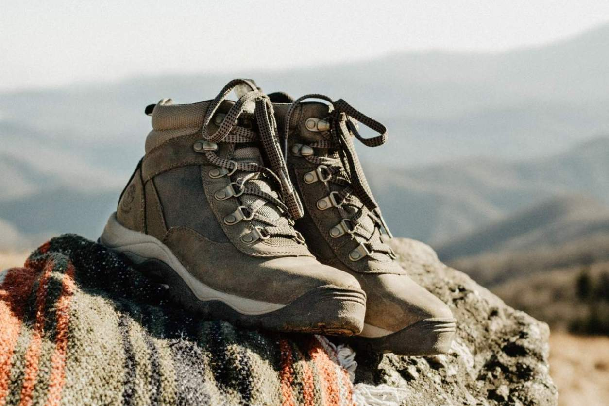 pair-of-hiking-boots-on-rock-on-mountain-road-trip-packing-list