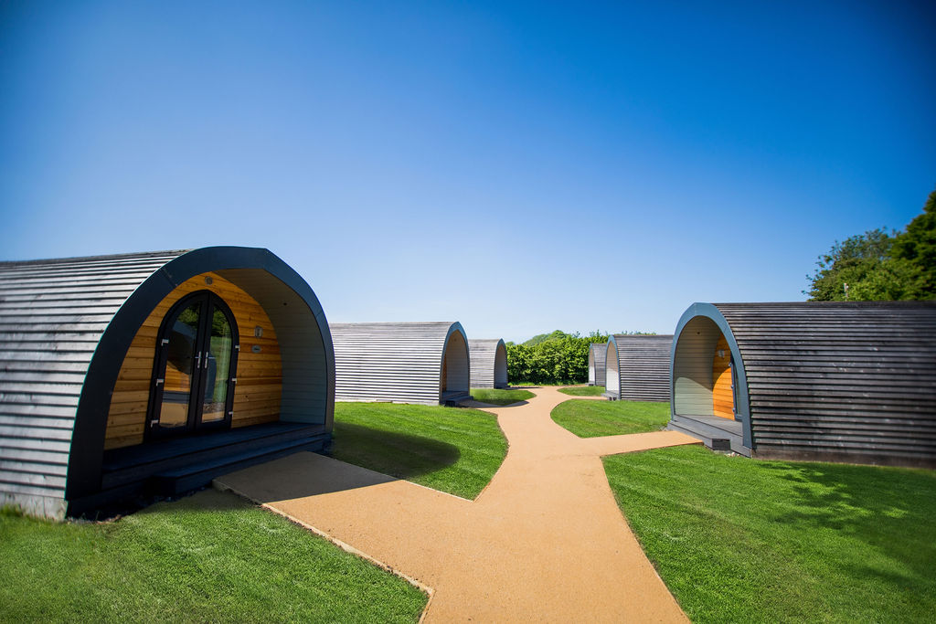 six-larch-clad-glamping-pods-in-field-on-sunny-day-glamping-gloucestershire