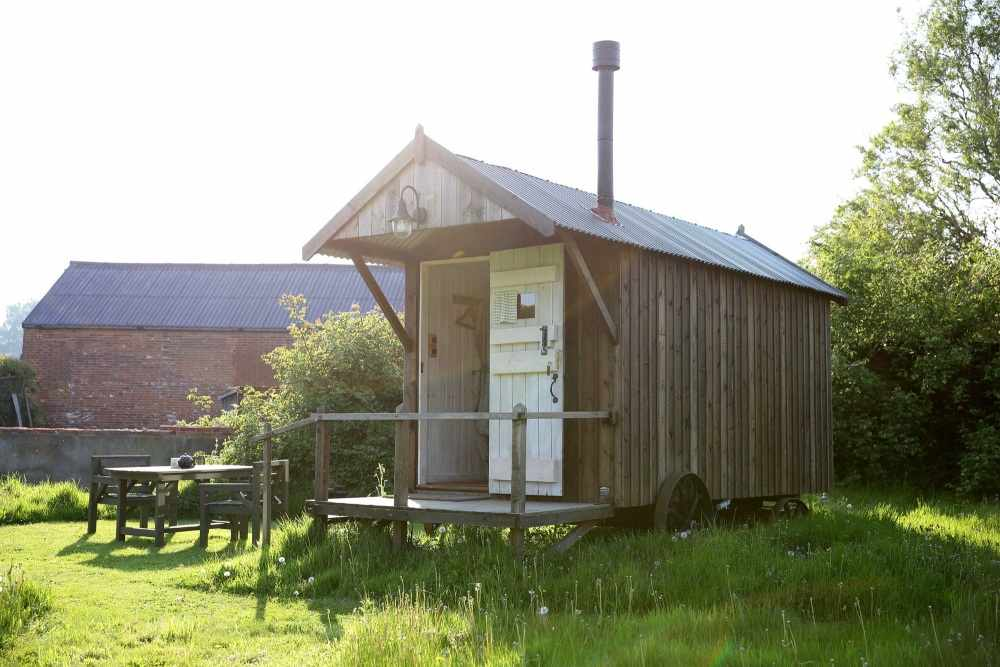 exterior-of-orchard-shepherds-hut-in-field-in-daytime
