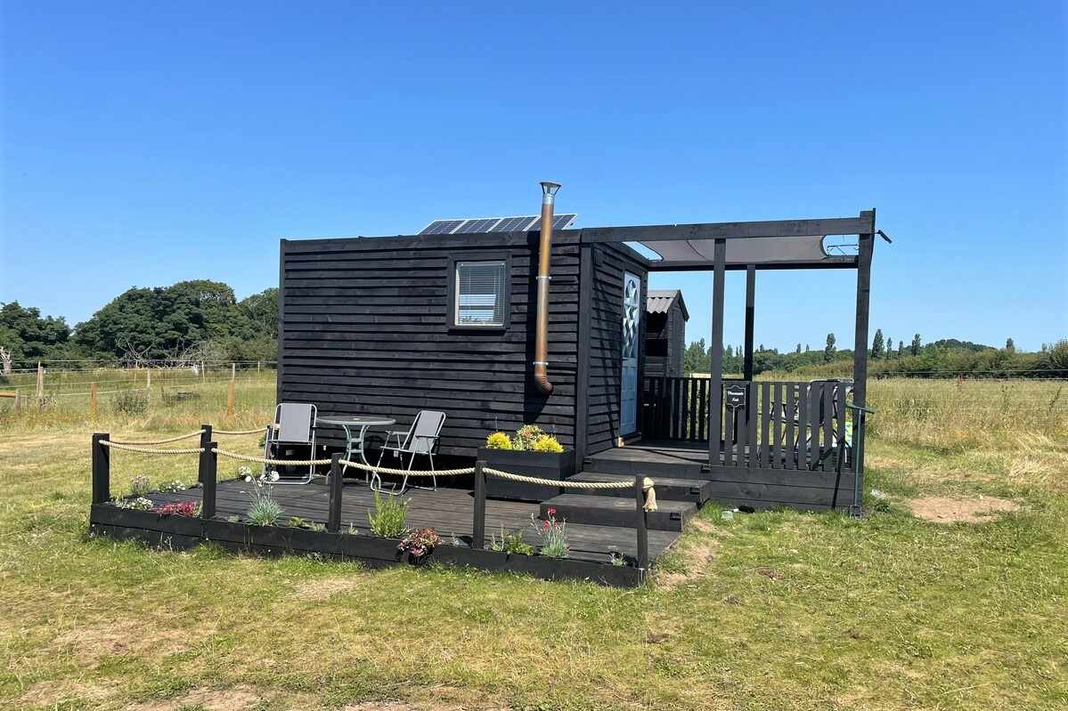 exterior-of-the-priory-shepherds-hut-in-field-in-daytime