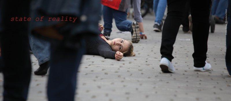 Eine junge Frau liegt auf dem gepflasterten Boden in einer Fußgängerzone. Menschen gehen vorbei. Die Frau schaut durch die Beine der Menschen in die Kamera.