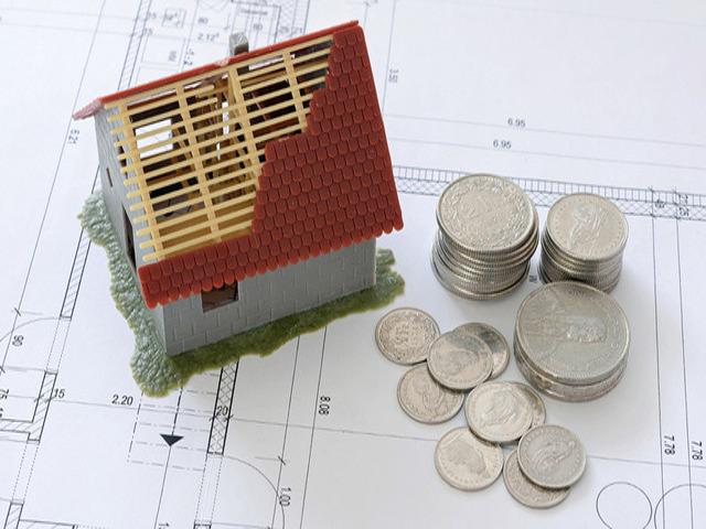 modellino di casa in costruzione posto sopra al progetto architettonico affiancato da monete ovvero un buon progetto della casa fa risparmiare soldi