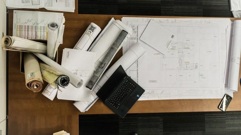 Tavolo di un architetto con progetti e computer