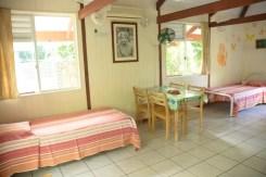 Grand bungalow : table à manger, lits simples, vue de la cuisine