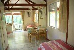 Grand bungalow : table à manger, lits simples vue de l'entrée