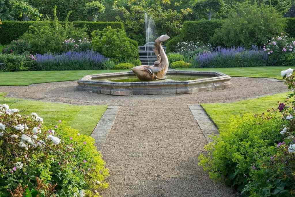 Coade-stone whale and mermaid fountain sculpted by Phillip Thomason in the rose garden at Farleigh Wallop