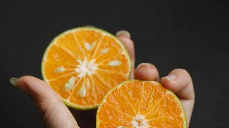 woman with halves of cut citrus fruit