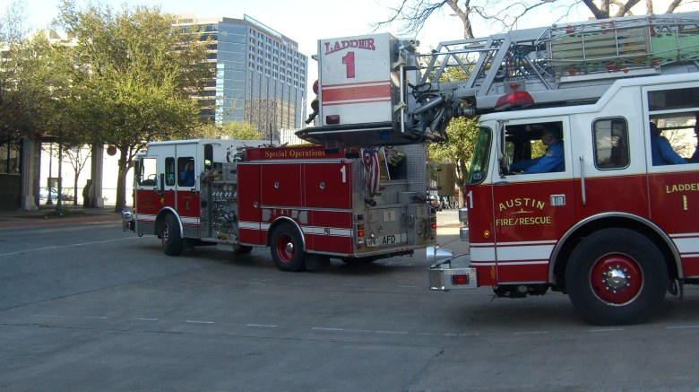 Two Austin Fire trucks pulling out of a fire station