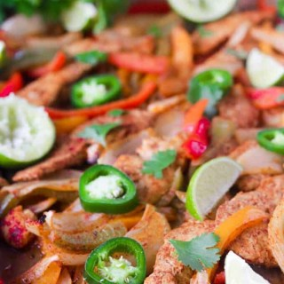 This Paleo and Whole30 Chicken Fajitas Sheet Pan Dinner is simple and easy with minimal cleanup! Serve it with some lime wedges, cilantro and guacamole.