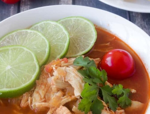 This Paleo and Whole30 Chicken Tortilla Soup is delicious, healthy and so easy to make! Just combine chicken breasts, onion and tomatoes in the slow cooker along with a few common spices like chili powder, garlic and cayenne and you have a scrumptious one pot slow cooker dinner! Garnish with limes, cilantro + avocado!