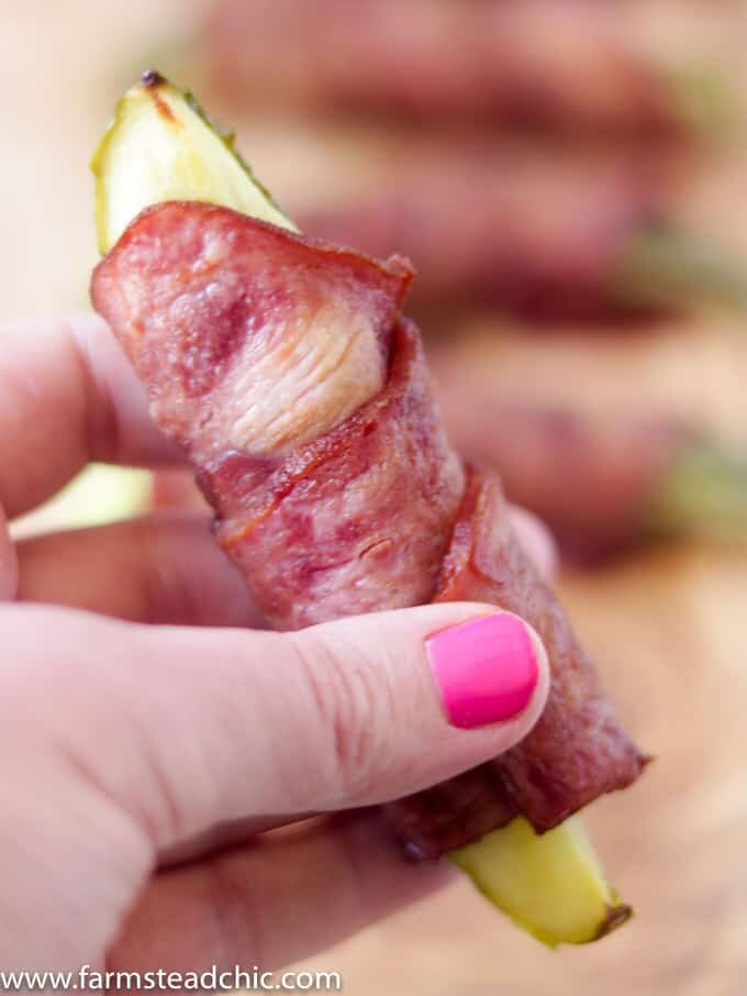 Bacon-wrapped pickles on a natural wood cutting board held by a woman with hot pink gel fingernails