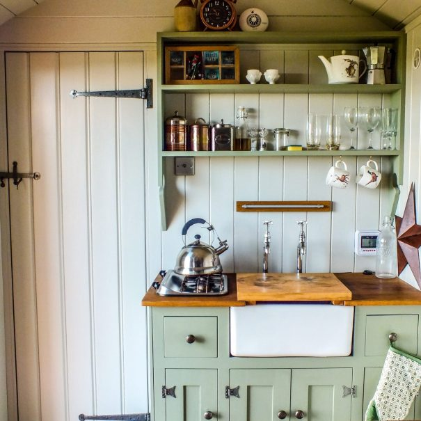 A small kitchen unit painted a nice green with a two ring gas hob and belfast sink