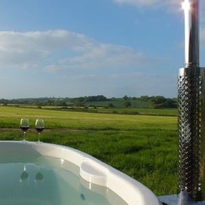 A woodfired hot tun looks out on the beautiful views at Farmstead Glamping