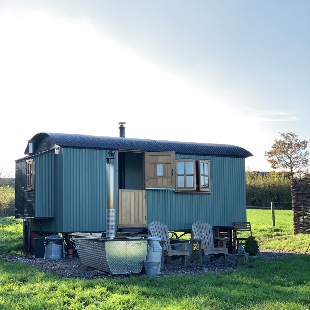 The pleasant Pheasant is a green shepherd hut sat in a field with chairs and a wood fired hot tub in front of it