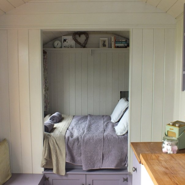 Inside of the shepherd hut showing a bed made up with purple bed spread and books on a shelf
