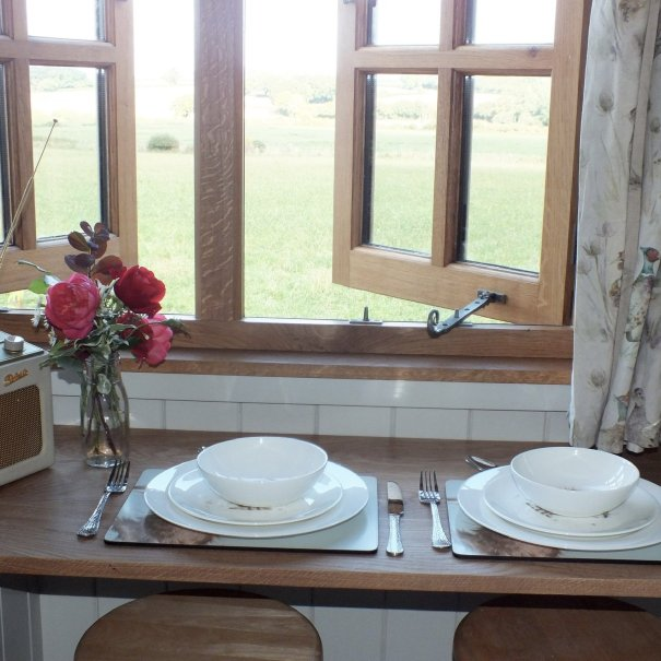 A small breakfast table is set ready to eat next to a bunch of flowers and a roberts radio with a view of farmland