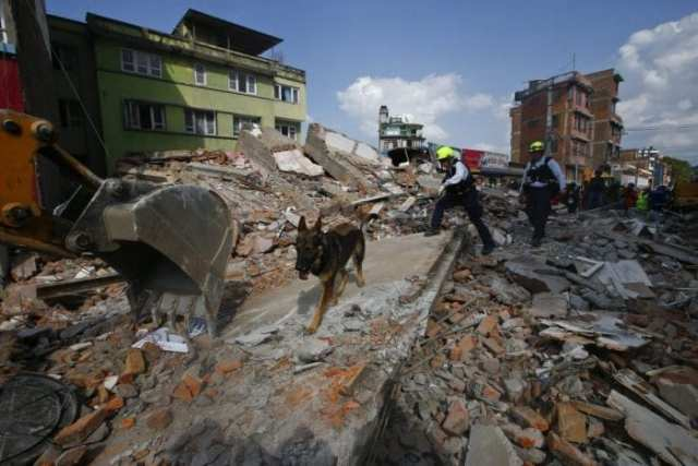 epa04744465 US rescue workers search for survivors at the site after a house collapsed during a strong earthquake, in Kathmandu, Nepal, 12 May 2015. More than 20 people were killed 12 May by the latest earthquake to hit the Himalayas, just 17 days after large parts of Nepal were levelled and more than 8,000 had died. A 7.4-magnitude quake caused the collapse of several buildings in Kathmandu and other areas of Nepal, officials said.  EPA/NARENDRA SHRESTHA