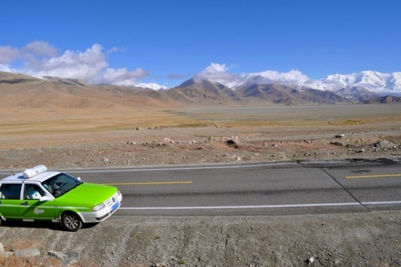 A taxi stops to see the beautiful scenery on the Karakoram Highway in Xinjiang, China