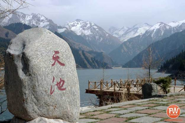 Xinjiang's Heavenly Lake with a stone marker bearing 天池 (the Chinese name)