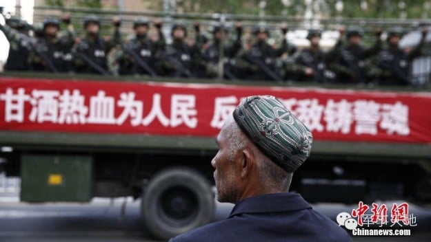 A Uyghur man watches a truck full of Chinese soldiers pass by in Urumqi, Xinjiang on May 24, 2014
