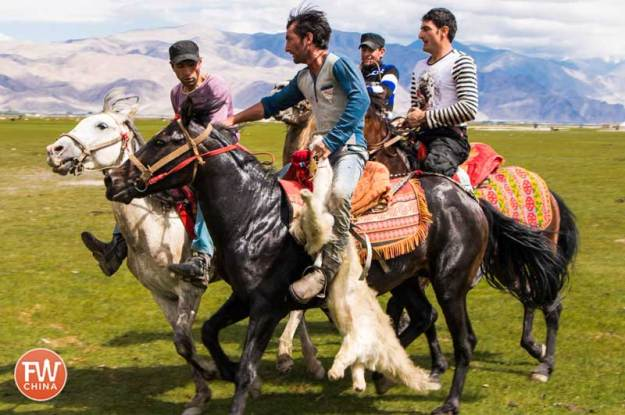 "Buzkashi riders in Tashkorgan carry the goat carcass ""ball"""
