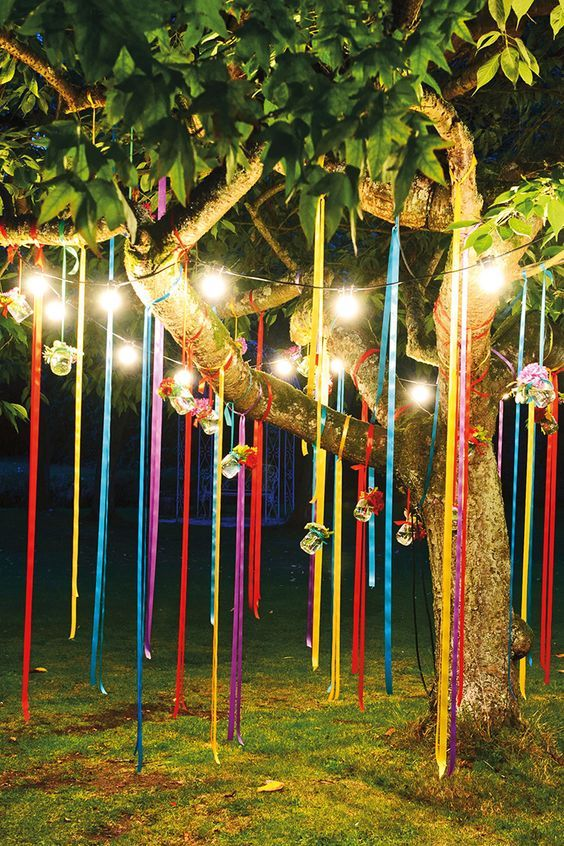 Real weddings - colourful flowers at the vibrant wedding of Fiona Kerr and Peter Brice, night shot of fairy lights and bright ribbons hanging from tree, jars of flowers