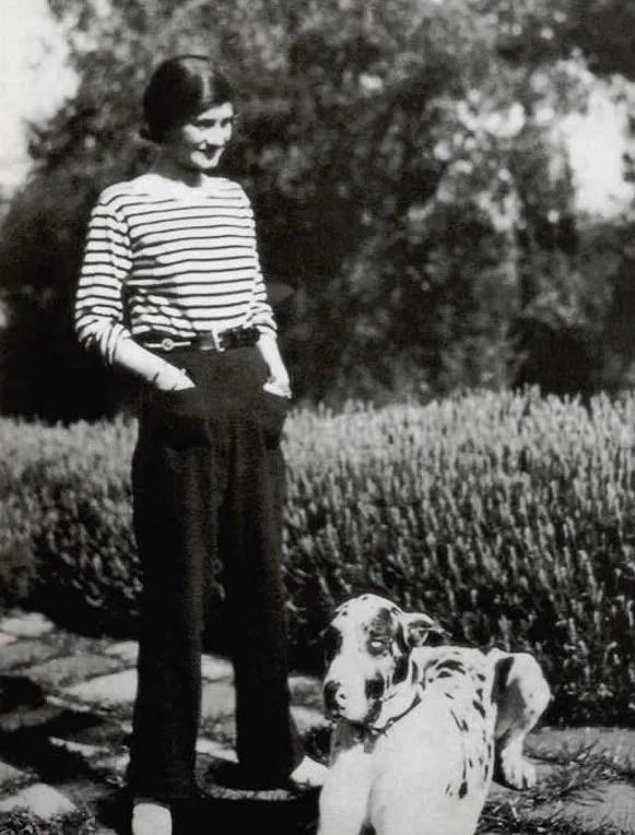 Coco Chanel posando ao lado de um cachorro