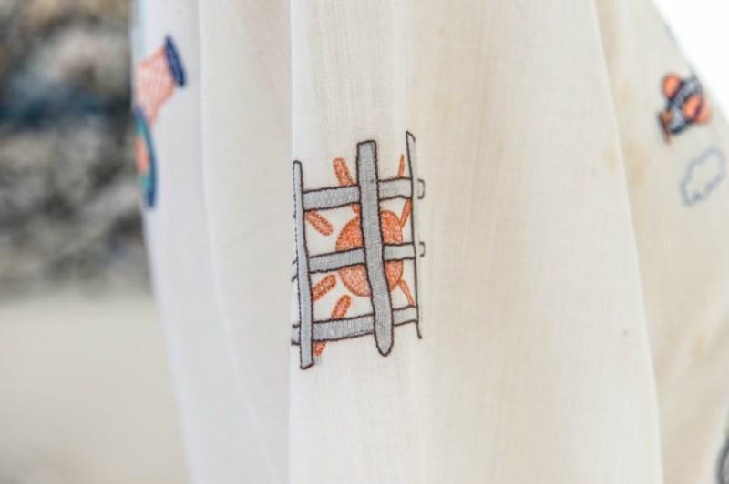 Bordado de um sol enjaulado em um dos vestidos de Zuzu Angel.