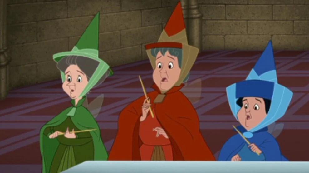 """Imagem das três fadas do filme """"A Bela Adormecida"""", Fauna, Flora e Primavera, vestidas com roupas inspiradas no traje gótico em azul, verde e vermelho, com chapéu pontiagudo e véu"""