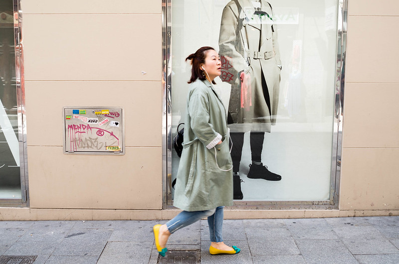 Mulher a passar por um cartaz de moda.