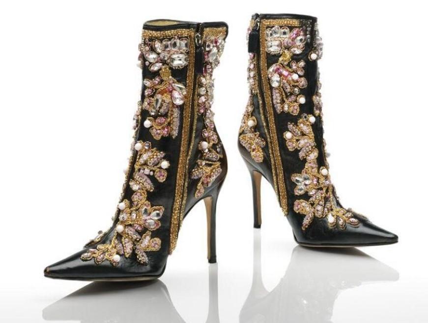 Foto de um par de botas pretas de couro de salto alto fino com zíper e adornadas com pedrarias e bordados dourados em um fundo branco