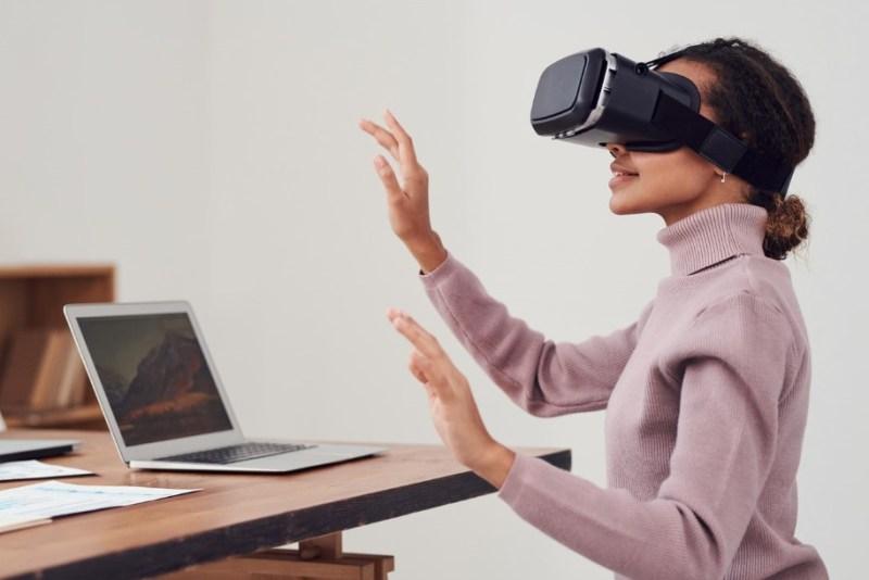 Mulher com aparelho de realidade virtual e computador. Ciberespaço.