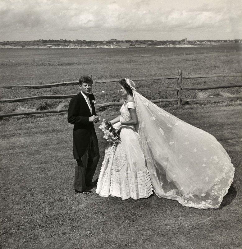 Foto de Jacqueline Kennedy com um vestido de noiva branco e véu transparente ao lado de John Kennedy após o seu casamento, em 1953.
