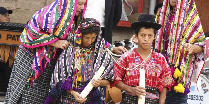 Foto de um cerimônia de casamento tradicional da Guatemala com um casal ao centro.