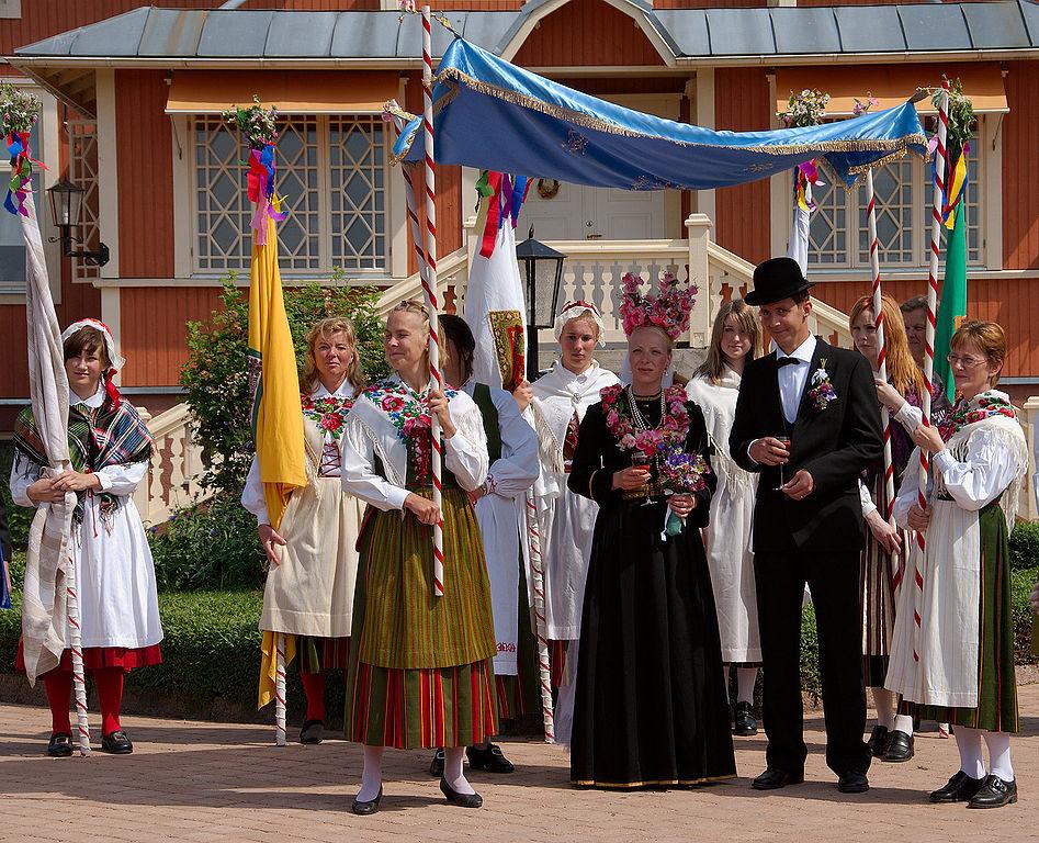 Festa de casamento em Jomala, interior da Finlândia, onde se vê um vestido de noiva preto ornamentado com flores.