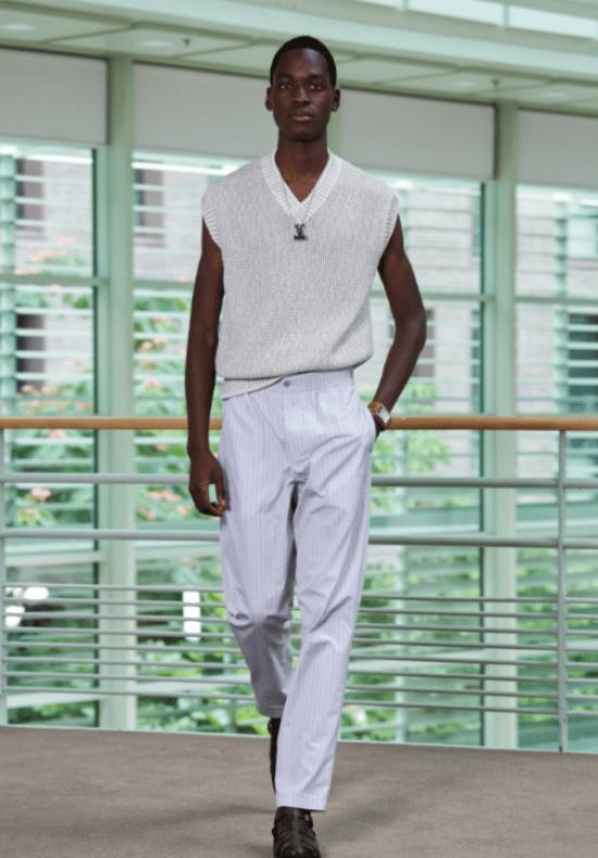 Modelo usa regata tricô gola v com ombro largo e calça alfaiataria