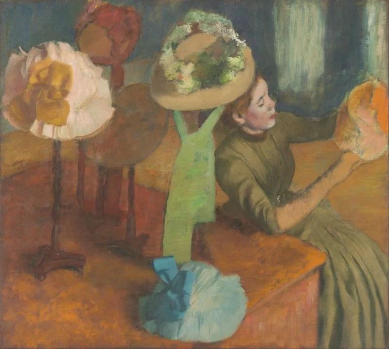 Mulher em uma chapelaria sentada com um chapéu na mão