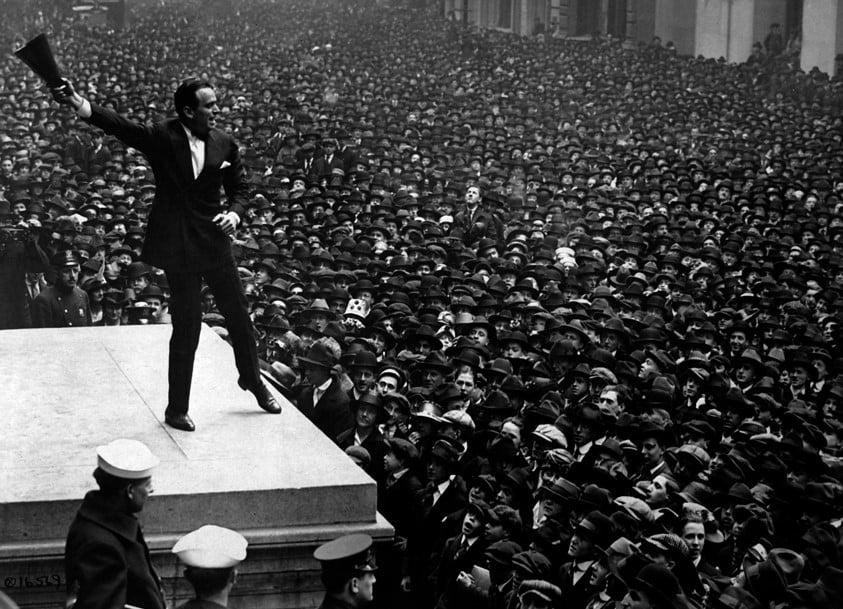 Homem a agitar uma multidão com um chapéu na mão