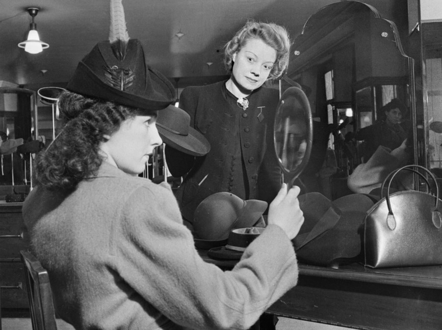 Foto em preto em branco de uma mulher provando um chapéu em uma chapelaria com um espelho na mão e sendo observada pela vendedora