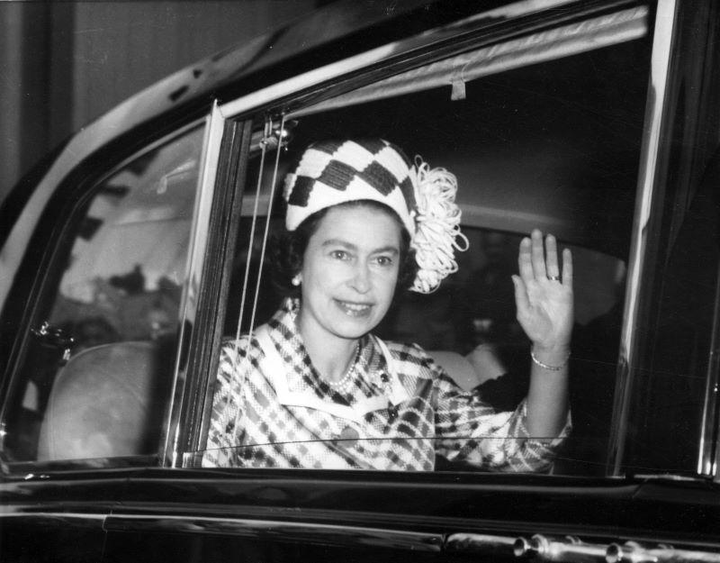 A rainha da Inglaterra Elizabeth II acenando de dentro de um carro