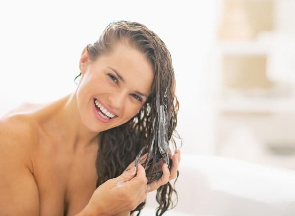 Foto de mulher aplicando condicionador aos cabelos - Como lavar os cabelos corretamente