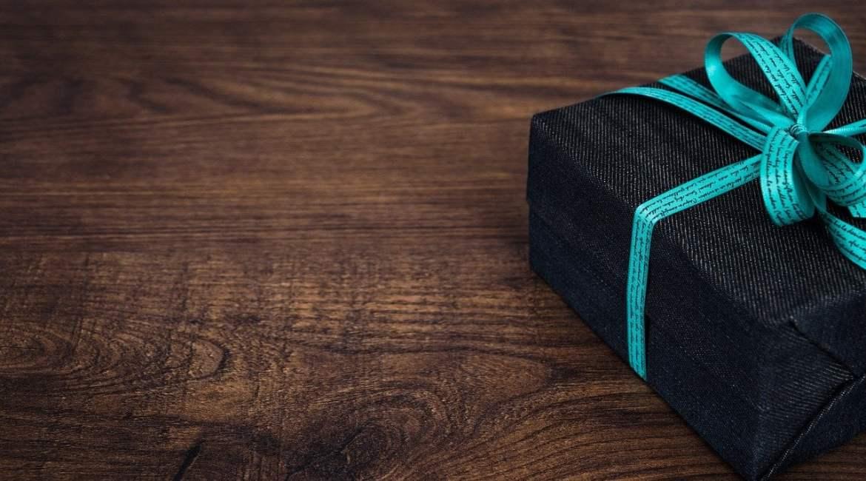 Foto de uma caixa de presente enrolada com fita azul em uma mesa de madeira