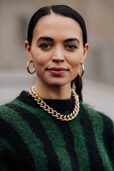 Foto de mulher com colar de correntes e brincos de argola